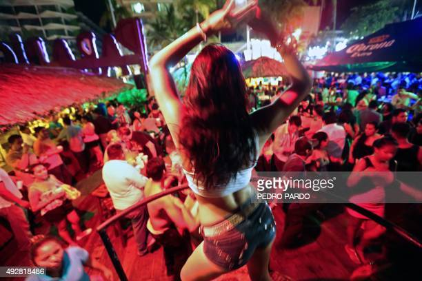 Tourists dance at a bar in the tourist city of Acapulco Guerrero State Mexico on October 4 2015 Acapulco once known as a celebrities refuge during...
