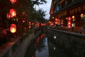 Tourists dine at restaurants and bars along an old canal on August 2 2006 in Lijiang ancient township of Yunnan Province China The Lijiang town has a...