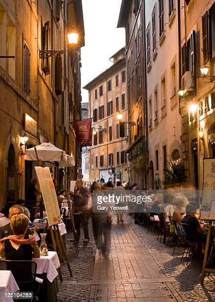 Tourists dining along cobbled street at dusk