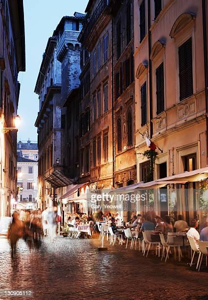 Tourists dining along narrow street at dusk