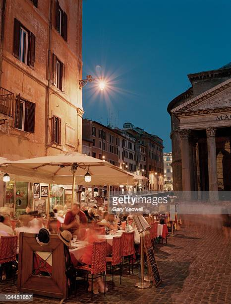 Tourists dining in a Piazza at dusk