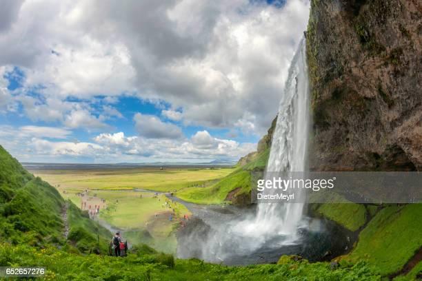 Tourists discover the Seljalandsfoss waterfall