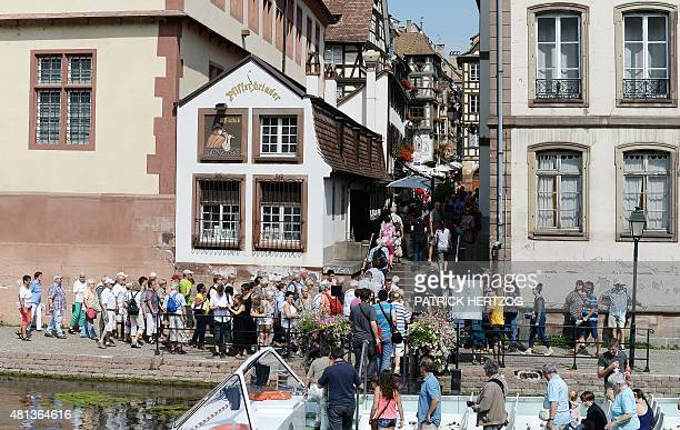 Tourists disembark from a boat tour as they visit the city of Strasbourg eastern France on July 19 2015 AFP PHOTO / PATRICK HERTZOG