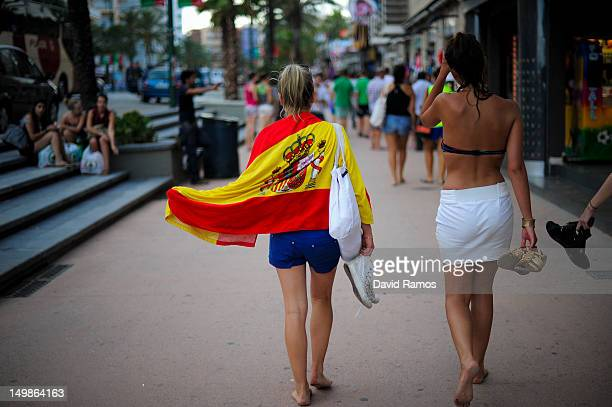 Tourists draped in a spanish flag walks along the main commercial street on August 5 2012 in Lloret de Mar Spain Tourism is the largest contributor...