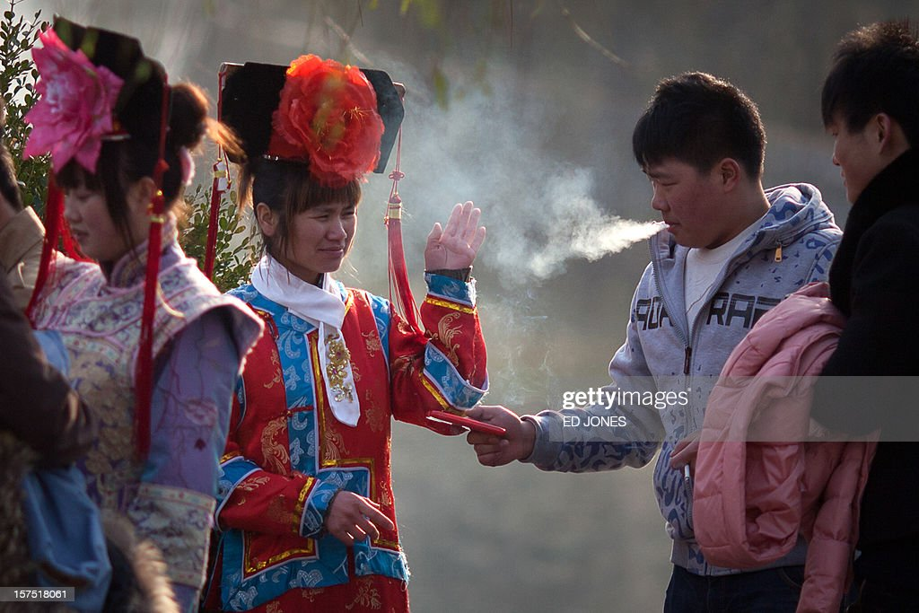 A tourists dressed in Qing dynasty style clothing waves away cigarette smoke as she stands with her companions in Beihai park in Beijing on December 4, 2012. The latest batch of purchasing managers' indexes from HSBC show manufacturing activity in China hit a 13-month high, while India also saw its strongest expansion since June. AFP PHOTO / Ed Jones