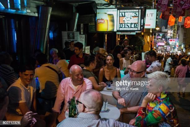 Tourists drink at Lan Kwai Fong a famous clubs street in Hong Kong on June 24 2017 in Hong Kong Hong Kong Hong Kong is marking 20 years since the...