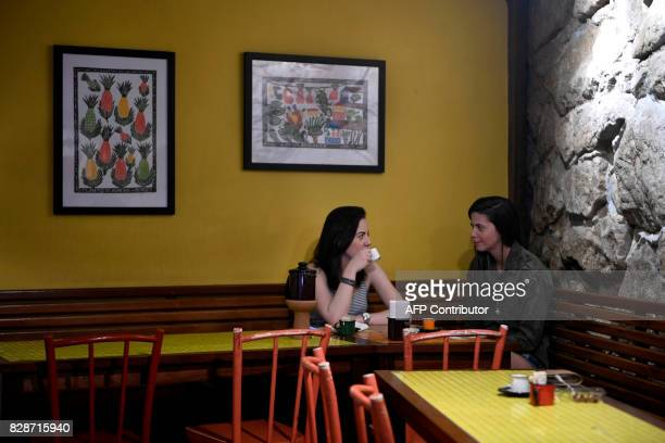 Tourists drink coffee at a restaurant in Santa Teresa neighborhood in Rio de Janeiro Brazil on July 27 2017 Bars and restaurants in Rio de Janeiro's...