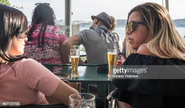 Tourists drink Super Bock draught beer at a terrace bar in the viewpoint of Santa Catarina a spot favored by visitors on October 01 2017 in Lisbon...