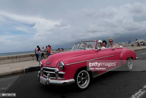 Tourists drive along the Maelecon in a classic car taxi on October 12 2017 in Havana Cuba