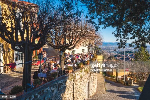 Tourists eating out in San Vigilio, Bergamo, Italy.