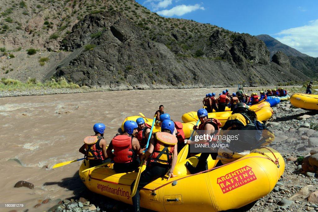 Tourists embark on the rafts to go rafting through the rapids in the muddy waters of the Mendoza river near Potrerillos, Argentina on January 29, 2013. AFP PHOTO / DANIEL GARCIA