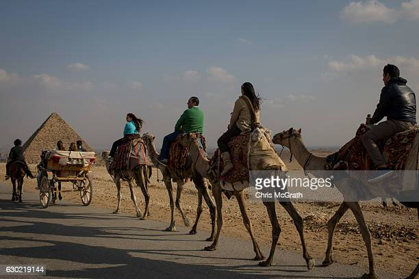 Tourists enjoy a camel ride around Egypt's famous Giza Pyramids on December 18 2016 in Cairo Egypt Since the 2011 Arab Spring and continued terrorist...