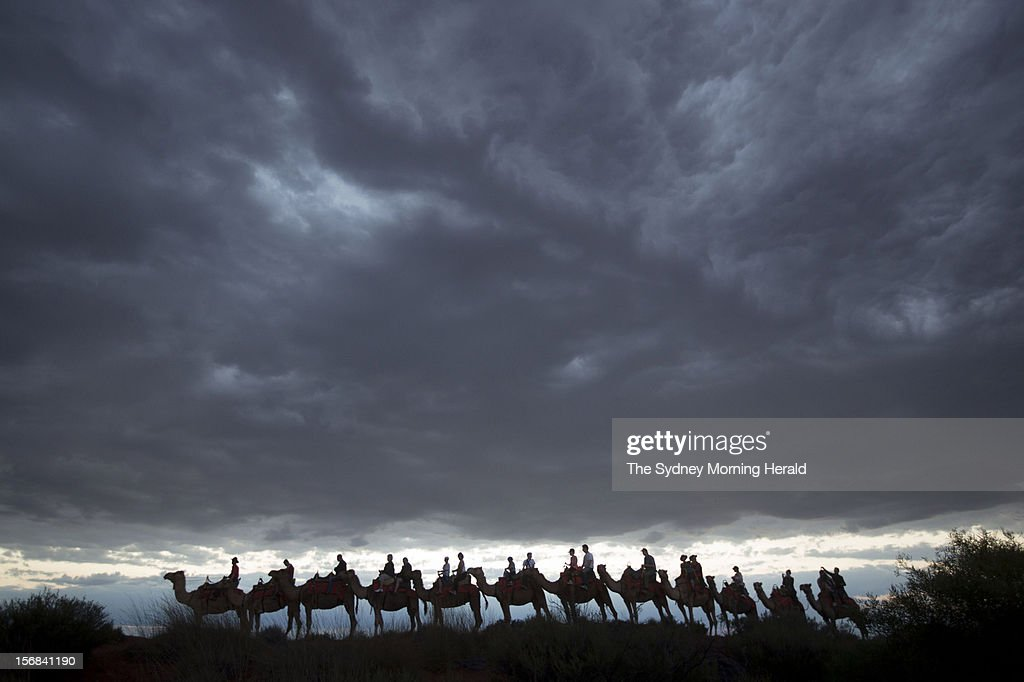 Tourists enjoy a camel ride at dawn at Uluru in Central Australia, November 5, 2012. (Photo by Glenn Campbell/The Sydney Morning Herald/Fairfax Media via Getty Images).