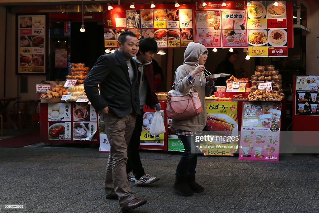 Tourists enjoy Chinese food as walk at the Nankinmachi China Town on February 8, 2016 in Kobe, Japan. In Nankinmachi, the district known as Kobe Chinatown, tourists enjoyed Chinese food, lion dance and the parade organized to celebrate the Lunar New Year.