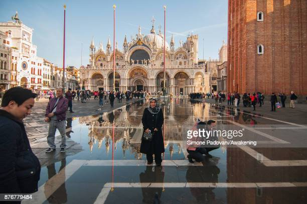 Tourists enjoy high water in St Mark Square on the day before the traditional Festa della Salute on November 20 2017 in Venice Italy The Festa della...