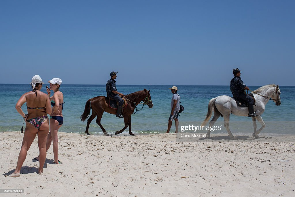 Tourists enjoy the beach as mounted police patrol the beach on June 25, 2016 in Sousse, Tunisia. Before the 2011 revolution, tourism in Tunisia accounted for approximately 7% of the countries GDP. The two 2015 terrorist attacks at the Bardo Museum and Sousse Beach saw tourism numbers plummet even further forcing hotels to close and many tourism and hospitality workers to lose their jobs. The 26th of June marks the first anniversary of the Sousse beach attacks.