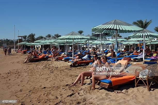 Tourists enjoy the beach in the Egyptian Red Sea resort of Sharm elSheikh on February 19 2014 The decline in tourism since the fall of Egyptian...