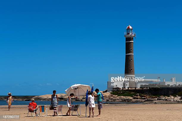 Tourists enjoy the beach near the lighthouse of Jose Ignacio next to Punta del Este one of the most exclusive seaside resorts of Latin America 140 km...