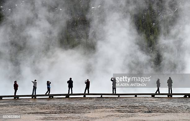 Tourists enjoy the Grand Prismatic Spring at the Midway Geyser Basin in Yellowstone National Park on May 11 2016 Yellowstone the first National Park...