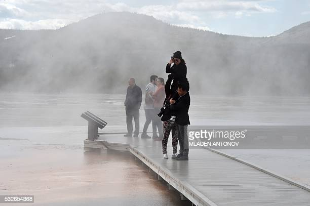 Tourists enjoy the Grand Prismatic Spring at the Midway Geyser Basin at Yellowstone National Park on May 11 2016 Yellowstone the first National Park...