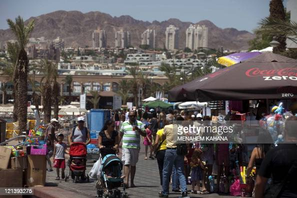 Tourists enjoy the promenade along the beach in the Red Sea Israeli resort city of Eilat on August 19 2011 Eight Israelis were killed in a string of...