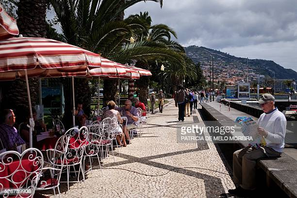 Tourists enjoy the sun in downtown Funchal on the Madeira island on April 30 2016 / AFP / PATRICIA DE MELO MOREIRA