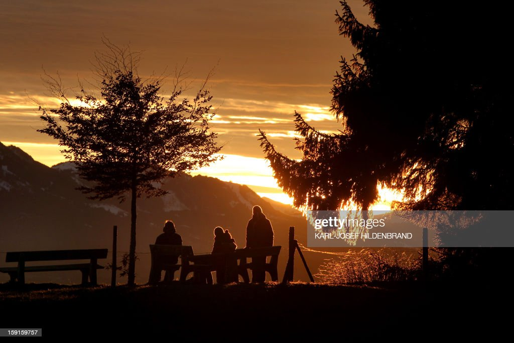 Tourists enjoy the view from the Auerberg mountain near Bernbeuren, southern Germany, as sun sets behind an Alps panorama on January 8, 2013.