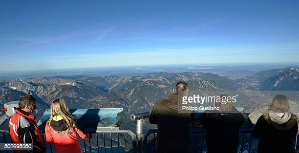 Tourists enjoy the view from the Zugspitze on a sunny day with temperatures of up to nine degrees Celsius in the German Alps on December 28 2015 near...