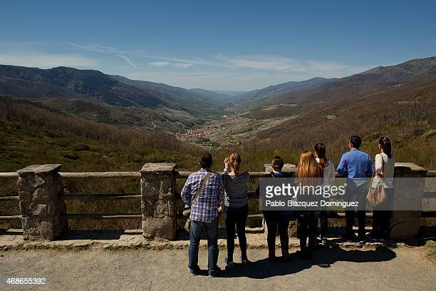 Tourists enjoy the view of the Jerte Valley from the high of the Tornavacas mountain pass during the cherry blooming season on April 5 2015 in the...