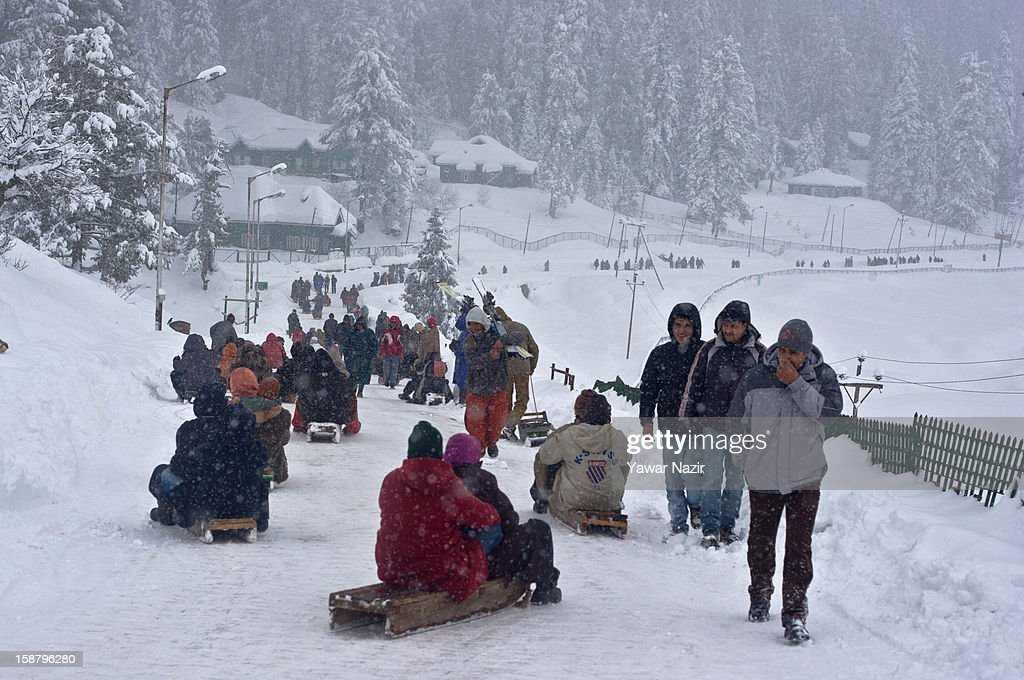 Tourists enjoy toboggan rides on the slopes during a snowfall on December 29, 2012 in Gulmarg, 54 km (35 miles) to the west of Srinagar, the summer capital of Indian-administered Kashmir, India. With the second round of heavy snowfall in Kashmir valley, skiers from around the globe have descended on the ski resort of Gulmarg, known for long-run skiing, snow-boarding, heli-skiing and steep mountains. Gulmarg is located less than six miles from the ceasefire line or Line of Control (LoC) that divides Kashmir between India and Pakistan. As a sense of normalcy has started to return to this strife-torn region, various foreign governments, including the United Kingdom, have lifted the travel advisory to its citizens traveling to Kashmir, raising the hopes of the local tourism industry, officials said.