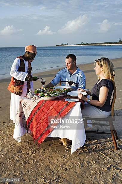 Tourists enjoying a romantic sunset seaside fish dinner at Benguerra Lodge. Mozambique. (MR)