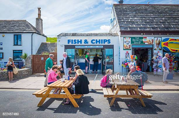Tourists enjoying fish and chips at seaside resort Dorset UK