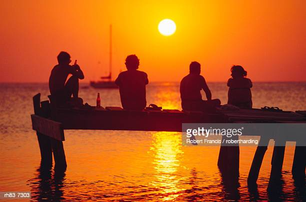 Tourists enjoying the sunset, Roatan, largest of the Bay Islands, Honduras, Caribbean Sea, Central America