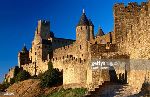 Tourists enter medieval walled city at sundown via Porte d'Aude, with Chateau Comtal in background, Carcassonne, France