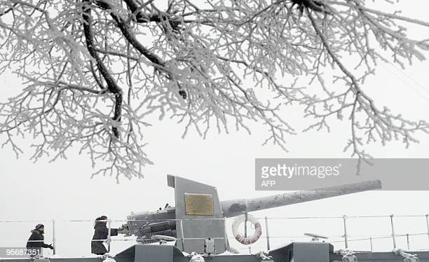 Tourists examine a snowcovered howitzer onboard the historic cruiser Aurora in St Petersburg on January 10 2010 Air temperature in the city has...