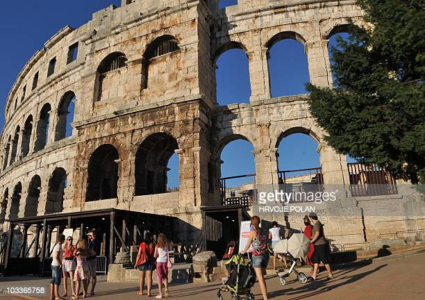 Tourists explore the old Roman amphitheatre Arena in northern Croatian Adriatic town of Pula on August 1 2010 The Arena is the only remaining Roman...