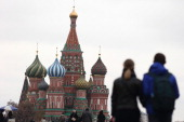 Tourists explore the Red Square in front of St Basil's Cathedral on October 31 2013 in Moscow Russia