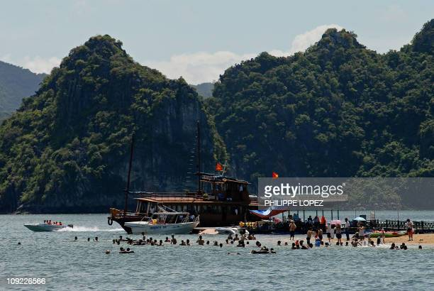 Tourists flock a tiny beach on the edge of a stone island of Halong Bay 08 July 2007 Vietnam received more than 2 million foreign visitors in the...