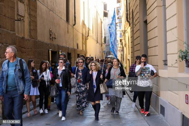Tourists follow a tour guide carrying a flag through a backstreet in Florence Italy on Friday Sept 22 2017 UK Prime Minister Theresa May will use a...