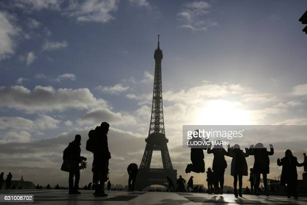 Tourists from Asia jump in the air as a souvenir photo is taken in front of the Eiffel Tower at sunrise in Paris on January 5 2017 / AFP / LUDOVIC...