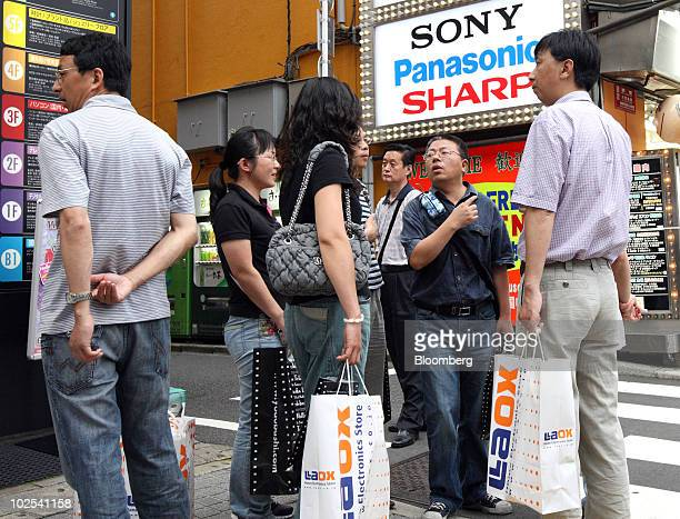 Tourists from China stand outside a Laox Co shop in the Akihabara district of Tokyo Japan on Wednesday June 30 2010 Chinese shoppers in Akihabara...