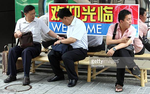 Tourists from China take a rest outside a Laox Co shop in the Akihabara district of Tokyo Japan on Wednesday June 30 2010 Chinese shoppers in...