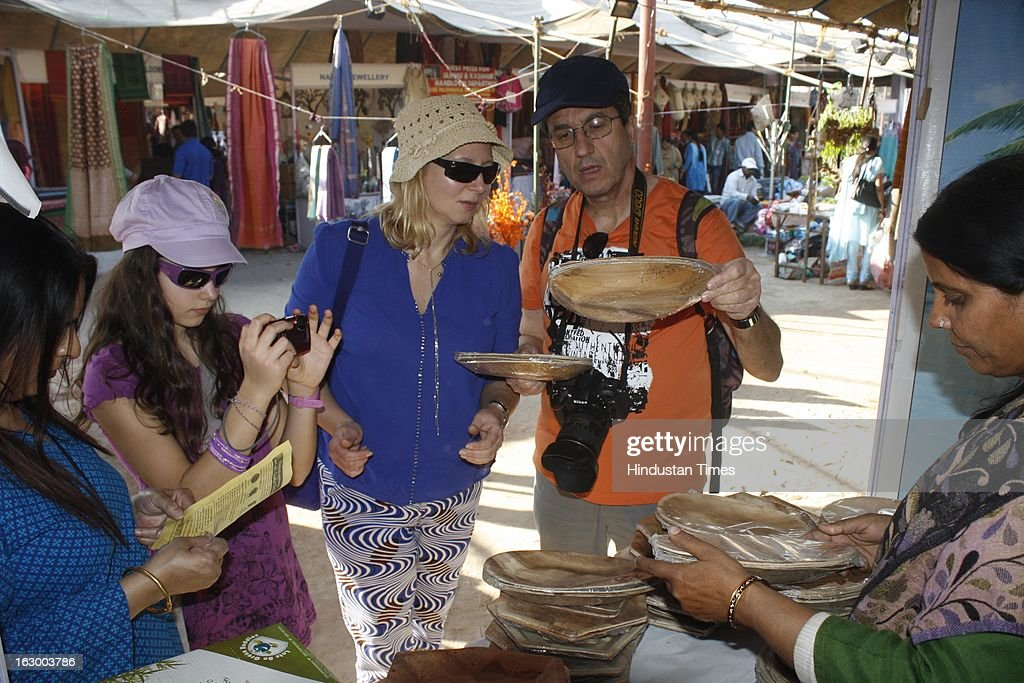Tourists from France buy Sanskruti Foodware products from a stall during the final day of Basant Utsav exhibition at Ramlila Ground Noida Stadium in Sector 21A on March 3, 2013 in Noida, India. Handmade products of different states are displayed on sale in the exhibition.