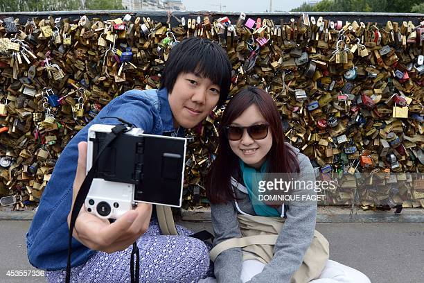 Tourists from Macau in China Lili and Aris take a selfie at the pont de l'archeveche where padlocks are attached to the railing on August 13 2014 in...
