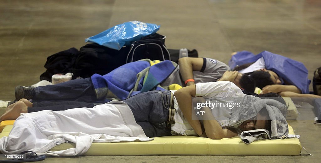 Tourists from Mexico City sleep in a shelter in Acapulco, Guerrero state, Mexico, on September 17, 2013 as heavy rains hit the country. At least 48 people were killed and thousands evacuated from towns on the Pacific and Gulf of Mexico coasts over the weekend as Tropical Storm Manuel and downgraded Hurricane Ingrid set off landslides and floods that damaged bridges, roads and homes. AFP PHOTO / PEDRO PARDO