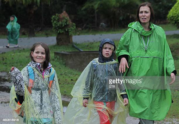Tourists from various countries walk after arriving at a school used as an evacuation centre in Jerantut a major town in central Pahang on December...