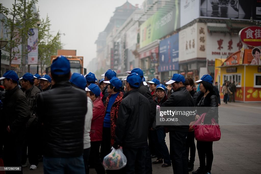 Tourists gather as they walk on a popular shopping street in Beijing on April 23, 2013. Manufacturing activity in China slowed in April due to sluggish foreign demand, HSBC said, in a sign of further weakness in the world's second-largest economy. AFP PHOTO / Ed Jones