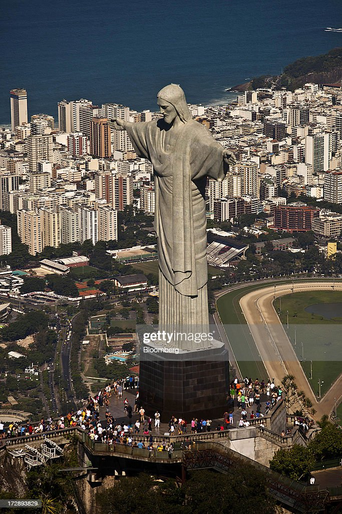 Tourists gather at the Christ the Redeemer statue on top of Corcovado Mountain in this aerial photograph of Rio de Janeiro, Brazil, on Thursday, July 4, 2013. Brazils shorter-term swap rates fell after a report showed inflation slowed in June more than analysts forecast, damping speculation that the central bank will increase borrowing costs at a faster pace. Photographer: Dado Galdieri/Bloomberg via Getty Images