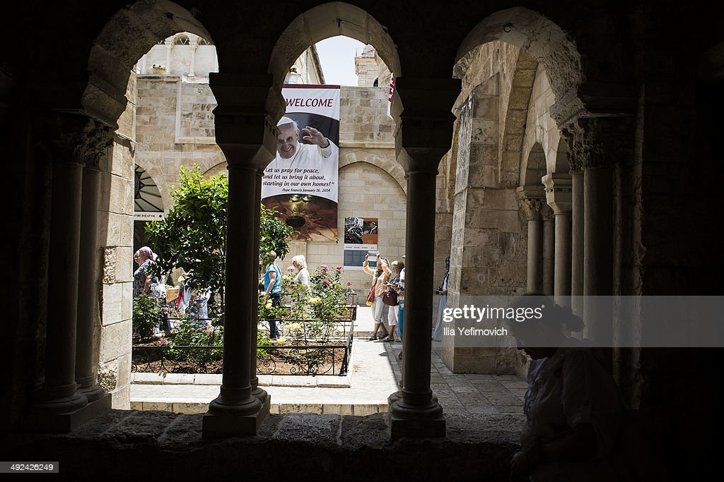 Tourists gather at the church of Nativity, taking pictures with poster of Pope Francis in the background on May 20, 2014 in Bethlehem, West Bank. Pope Francis is due to make his first visit to the Holy Land as pontiff and will visit both the West Bank and Israel this coming Sunday. The Pope will celebrate two public Masses during his visit, one in Amman, Jordan and the other in Manger Square in Bethlehem.