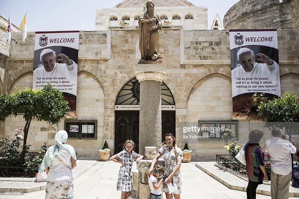 Tourists gather at the church of Nativity, tin front of posters of Pope Francis on May 20, 2014 in Bethlehem, West Bank. Pope Francis is due to make his first visit to the Holy Land as pontiff and will visit both the West Bank and Israel this coming Sunday. The Pope will celebrate two public Masses during his visit, one in Amman, Jordan and the other in Manger Square in Bethlehem.